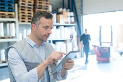 Man warehouse worker with tablet royalty free stock photos