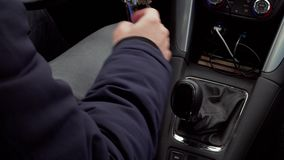 Mechanical gear shift knob, speed control during driving car. Man in warm clothes changing gear during car driving, mechanical speed control at day. Bunch of stock video