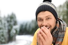Man in warm clothes outdoors, space for text. Winter vacation stock photo