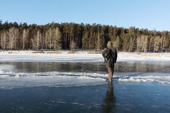 Man in warm clothes standing on the thin ice of a frozen river, Stock Image