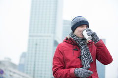 Man in warm clothing drinking coffee outdoors Stock Photos