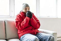 A Man With Warm Clothing Feeling The Cold Inside House on the sofa. Man With Warm Clothing Feeling The Cold Inside House on the sofa stock photography
