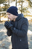 Man in warm clothing shivering while having a walk in forest Stock Photos
