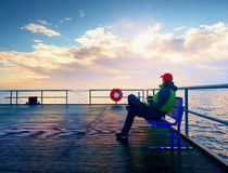 Man in warm jacket and baseball cap sit on mole bench and enjoy morning at sea. Stock Photography