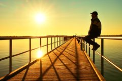 Man in warm jacket and baseball cap sit on pier handrail construction and enjoy morning at sea. Stock Photo