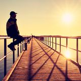 Man in warm jacket and baseball cap sit on pier handrail construction and enjoy morning at sea. Stock Photography