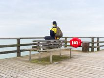 Man in warm jacket and baseball cap sit on wooden pier and enjoy quiet morning sea. Tourist relax stock photos
