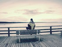 Man in warm jacket and baseball cap sit on wooden pier and enjoy quiet morning sea. Tourist relax royalty free stock photos