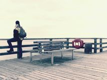 Man in warm jacket and baseball cap sit on wooden pier and enjoy quiet morning sea. Tourist relax stock image