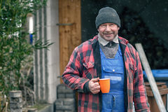 Man in a warm jacket and beanie drinking coffee Stock Images