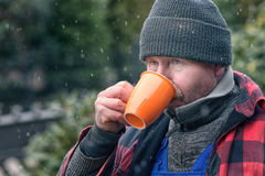 Man in a warm jacket and beanie drinking coffee Royalty Free Stock Photos