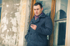 The man in warm jacket with mobile phone Royalty Free Stock Images