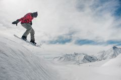 Man is jumping on a snowboard against a snow-capped mountain peaks stock images