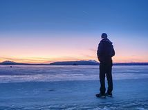 Man in warm suit gesture to morning horizon. Hiker stay on ice royalty free stock photos