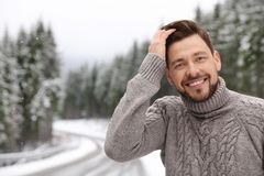 Man in warm sweater outdoors on snowy day, space for text. Winter vacation stock photography