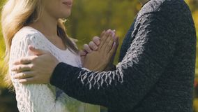 Man warming girlfriend on cold autumn day, rubbing her hands, care for loved. Stock footage stock video footage