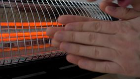 Man warming his hands near the heater. 4K