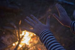 Fire warms up hands. Man warming up hands over fire stock images
