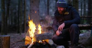 Man warms himself at camp fire in the woods. One pensive man with beard warms himself by the campfire outdoors in the woods a cold winter evening. Bonfire in the stock video