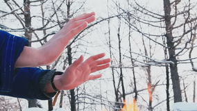 A man warms himself in the winter by the fire stock video
