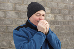 Man warms his hands in cold weather. Man warms his hands from the cold winter Royalty Free Stock Photos