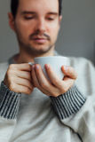 Man warms his hands with a cup of tea. Man warms his hands with a cup of hot tea Royalty Free Stock Image
