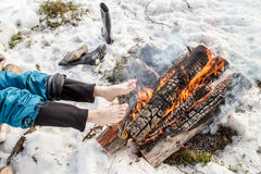 A man warms near the fire in the forest covered with snow. A man warms his barefoot feet near the fire in the pine forest covered with snow in winter Royalty Free Stock Photos