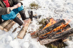 A man warms near the fire in the forest covered with snow. A man warms his hands and feet near the fire in the pine forest covered with snow in winter Stock Photos