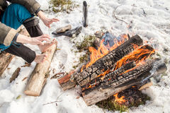 A man warms near the fire in the forest covered with snow. A man warms his hands and feet near the fire in the pine forest covered with snow in winter Royalty Free Stock Photography