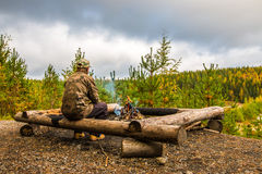 A man warms sausages above the campfire in Finland. The man has a camouflage clothes. In the background is the autumn forest Royalty Free Stock Photos