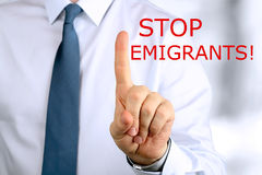 Man warning. Stop emigrants. Blue background behind Stock Photography