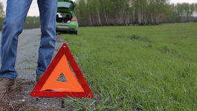 Man and warning triangle on the road. Car failure in the forest stock video