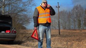 Man with warning triangle talking on the cell phone near car stock video