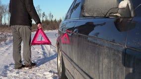 Man with warning triangle walking near car in winter stock video