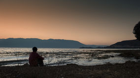 Man was sitting by the erhai lake Royalty Free Stock Image