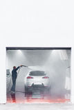 Man wash car by pressurized water at service station. Man washing car by pressurized water at garage. Complex service maintenance for automobiles. free space for Royalty Free Stock Photo