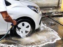 Man wash en bil vid handen genom att använda en skumförberedelse för polering, bilar i en carwash royaltyfri fotografi