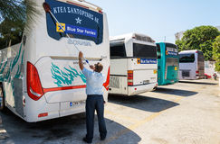 Man washes bus windows at bus station. THIRA, SANTORINI, GREECE -AUGUST 2015: Man washes bus windows at bus station on Santorini island, Greece Stock Photography