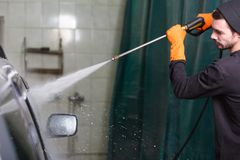 A man washes a car with a rubber hose. A man washes a grey car with the help of a rubber hose, transporting a stream of water on its surface stock photos