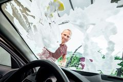 Man washes car  window glass, inside the car camera view Royalty Free Stock Image