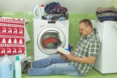 A man washes clothes in the washing machine. Housework men. Man helping his wife when washing clothes. Stock Photo