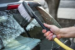 A man washes a gray car. With a brush Royalty Free Stock Images