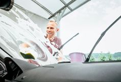 Man washes his car windshield window inside the car camera view stock images