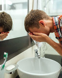 Man washes his face with spray Royalty Free Stock Photography