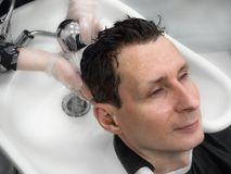 Man washes his hair after a haircut royalty free stock photo