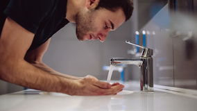 A man washes his hands and face stock video