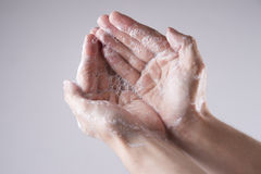A man washes his hands with soap and water. On a gray background Royalty Free Stock Photos