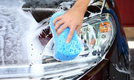 Man washing automobile headlight. With sponge Royalty Free Stock Photography