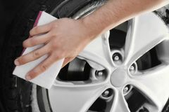Man washing automobile wheel with sponge. Closeup Stock Image