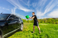 Man Washing Black Car in Green Field Stock Image